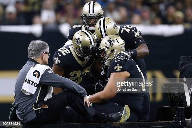 Andrus Peat of the New Orleans Saints is consoled by teammates as he is carted of the field during the first half of the NFC Wild Card playoff game...