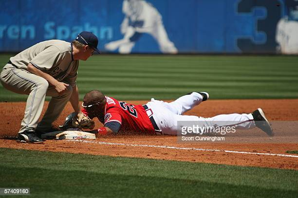 Andruw Jones of the Atlanta Braves dives in to third base despite the tag attempt by Geoff Blum of the San Diego Padres at Turner Field on April 16...