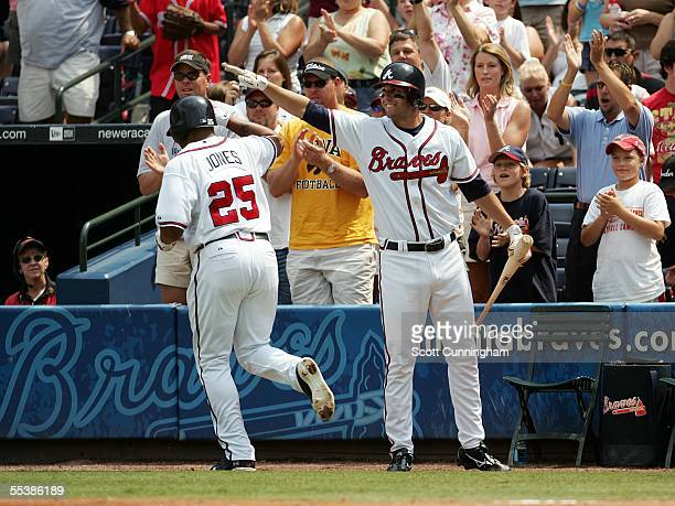 Andruw Jones of the Atlanta Braves is congratulated by Jeff Francoeur after hitting a home run against the New York Mets at Turner Field on September...