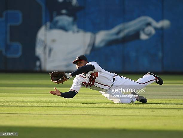 Andruw Jones of the Atlanta Braves makes a diving catch against the Cincinnati Reds at Turner Field July 16 2007 in Atlanta Georgia The Reds defeated...