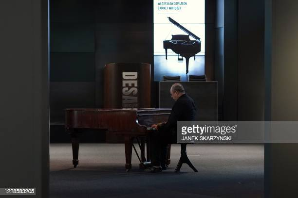 Andrzej Szpilman, the son of Wladyslaw Szpilman, plays a Steinway grand piano owned by his father in Warsaw on September 15, 2020. - A fountain pen,...