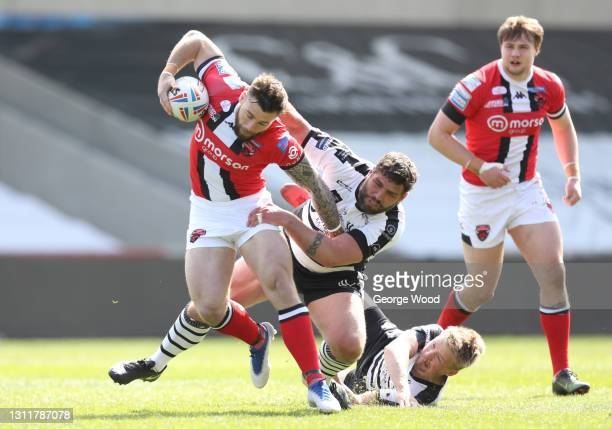Andy Ackers of Salford Red Devils breaks away from Lee Jewitt of Widnes Vikings during the Betfred Challenge Cup match between Salford Red Devils and...