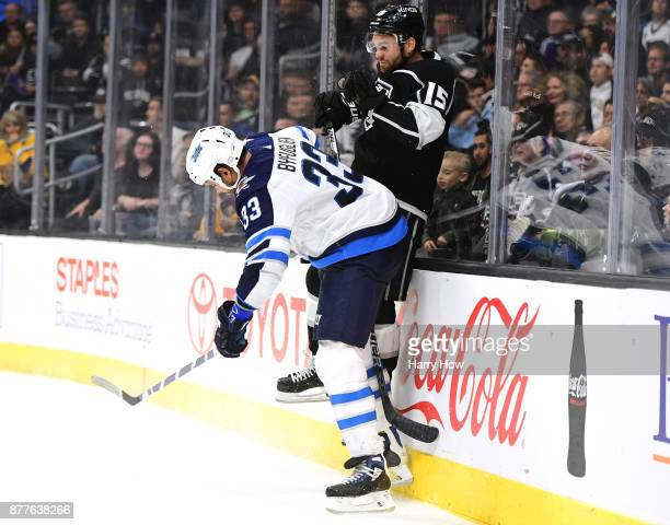 Andy Andreoff of the Los Angeles Kings takes a check from Dustin Byfuglien of the Winnipeg Jets during the second period at Staples Center on...