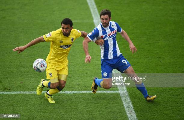 Andy Barcham of AFC Wimbledon battles with Will Grigg of Wigan Athletic during the Sky Bet League One match between Wigan Athletic and AFC Wimbledon...