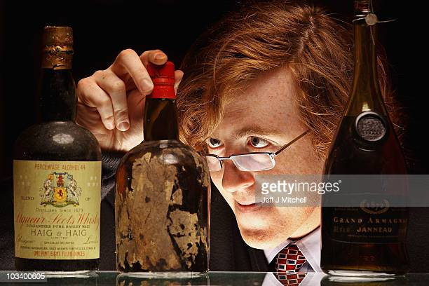Andy Bell, whisky specialist at McTears auctioneers holds a rare Victorian era whiskies on August 16, 2010 in Glasgow, Scotland. The two bottles of...