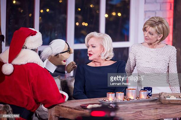 Andy Borg as Santa Borg Angelika Milster and Angelika Milster talk to a hand puppet representing Karl Lagerfeld during the 'Heiligabend mit Carmen...