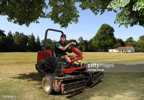Andy Boyce the groundsman of Hinton Charterhouse Cricket Club poses on his mower during ground preparations for a nets session carried out under new...