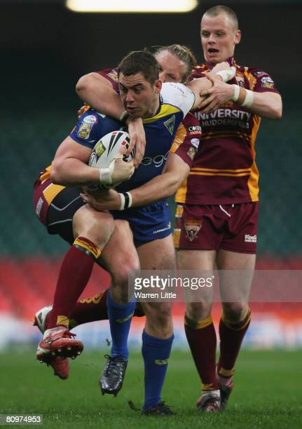 Andy Bracek of Warrington is tackled by Eorl Crabtree and Kevin Brown of Huddersfield during the engage Super League 'Millennium Magic' match between...