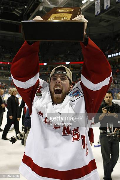 Andy Brandt of Wisconsin hoists the trophy and celebrates after the Badgers defeating Boston College 2-1 in the NCAA Mens Hockey National...
