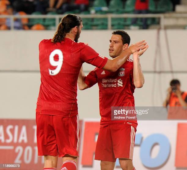 Andy Carroll of Liverpool celebrates with Maxi Rodriguez after scoring his goal during the preseason friendly match between Guangdong Sunray Cave and...