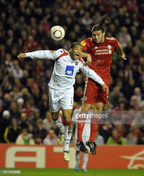 Andy Carroll of Liverpool competes for a high ball with Alberto Rodriguez of Braga during the UEFA Europa League Round of 16 second leg match between...