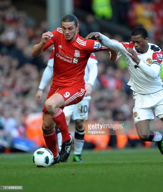 Andy Carroll of Liverpool is challenged by Patrice Evra of Manchester United during the Barclays Premier League match between Liverpool and...