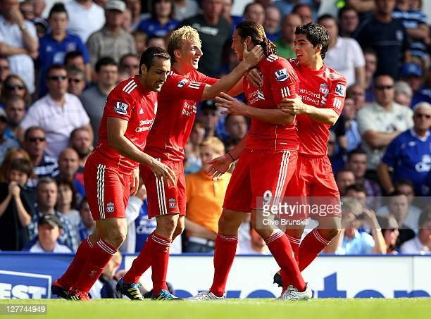 Andy Carroll of Liverpool is congratulated by Dirk Kuyt and his team mates after scoring the opening goal during the Barclays Premier League match...