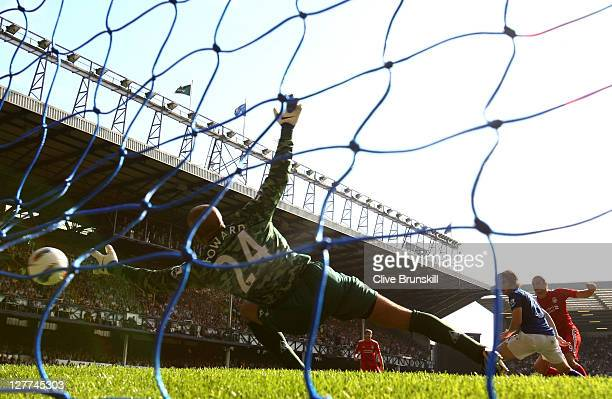 Andy Carroll of Liverpool scores the opening goal past Tim Howard of Everton during the Barclays Premier League match between Everton and Liverpool...