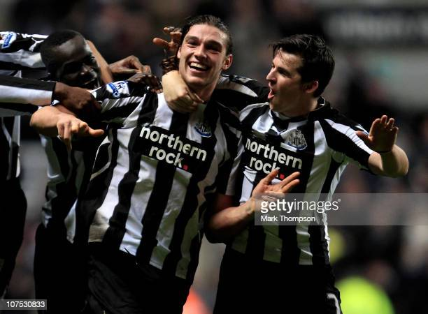 Andy Carroll of Newcastle United celebrates scoring his team's third goal with team mate Joey Barton during the Barclays Premier League match between...