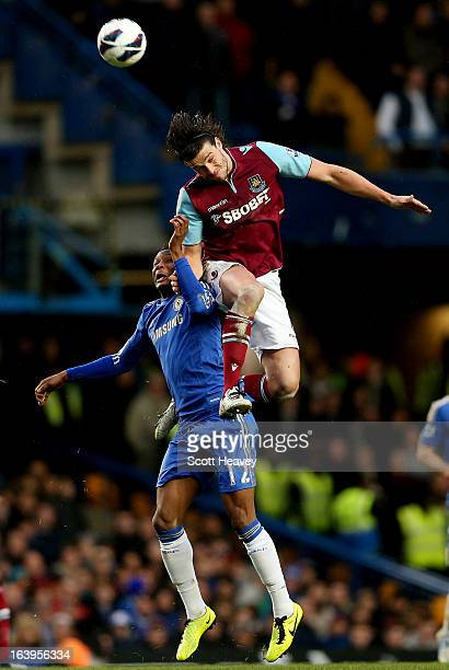 Andy Carroll of West Ham challenges John Obi Mikel of Chelsea during the Barclays Premier League match between Chelsea and West Ham United at...