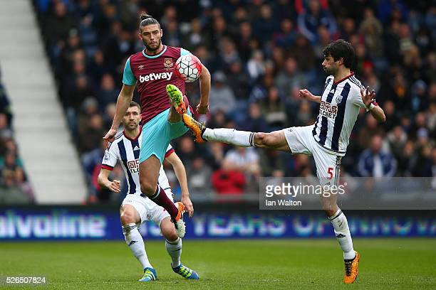 Andy Carroll of West Ham United and Claudio Yacob of West Bromwich Albion compete for the ball during the Barclays Premier League match between West...