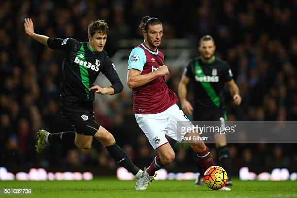 Andy Carroll of West Ham United and Philipp Wollscheid of Stoke City compete for the ball during the Barclays Premier League match between West Ham...