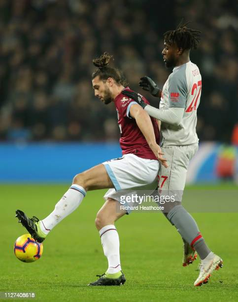 Andy Carroll of West Ham United battles for possession with Divock Origi of Liverpool during the Premier League match between West Ham United and...