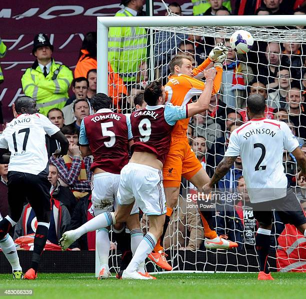 Andy Carroll of West Ham United challenges goalkeeper Simon Mignolet of Liverpool shortly before his teammate Guy Demel scored their first equalising...