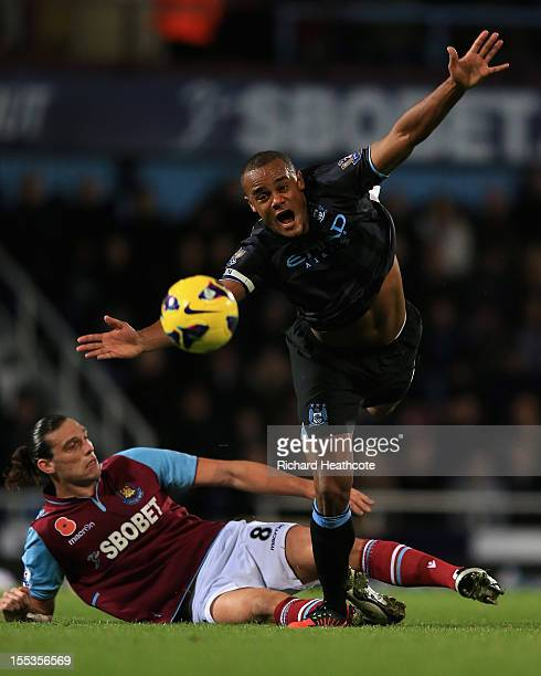 Andy Carroll of West Ham United challenges Vincent Kompany of Manchester City during the Barclays Premier League match between West Ham United and...