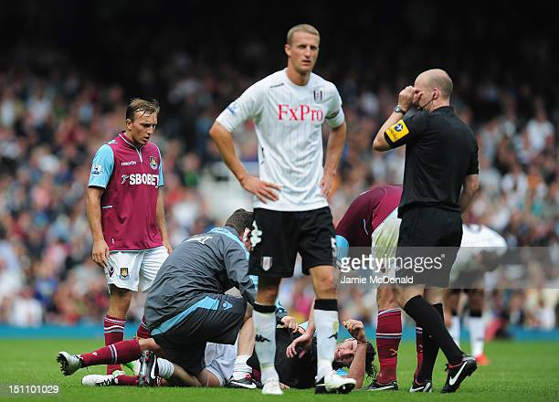 Andy Carroll of West Ham United clashes with Brede Hangeland of Fulham and is forced to leave the pitch during the Barclays Premier League match...