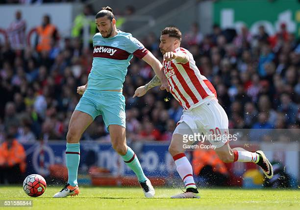 Andy Carroll of West Ham United holds off Geoff Cameron of Stoke City during the Barclays Premier League match between Stoke City and West Ham United...