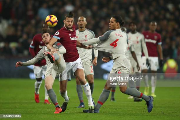 Andy Carroll of West Ham United in action with Virgil van Dijk and Andrew Robertson of Liverpool during the Premier League match between West Ham...
