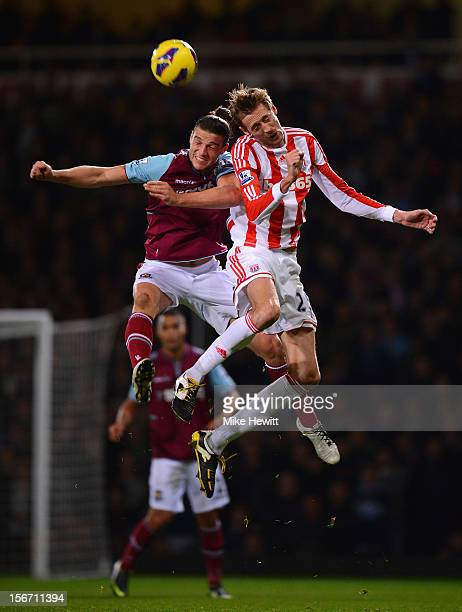 Andy Carroll of West Ham United jumps for a header with Peter Crouch of Stoke City during the Barclays Premier League match between West Ham United...