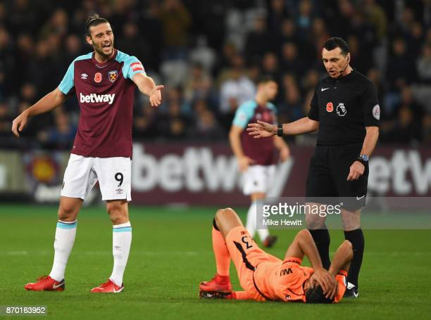 Andy Carroll of West Ham United reacts as Emre Can of Liverpool lies injured during the Premier League match between West Ham United and Liverpool at...