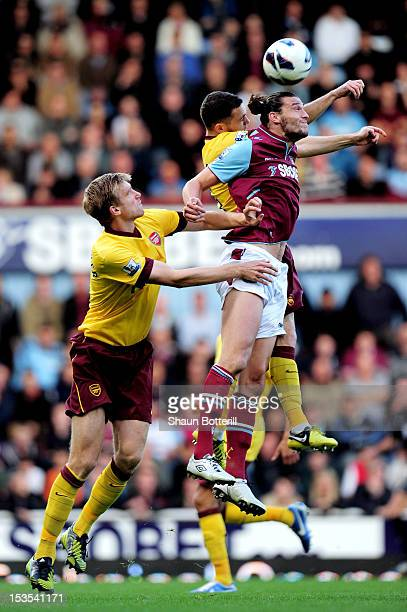 Andy Carroll of West Ham wins a header under pressure from Per Mertesacker and Thomas Vermaelen of Arsenal during the Barclays Premier League match...