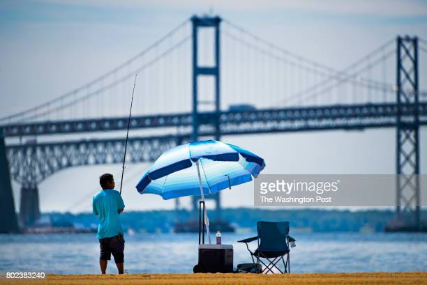Andy Chen age 29 from Frederick MD casts for rockfish on a beautiful sunny day at Sandy Point State Park in Annapolis MD on June 27 2017 The beach...