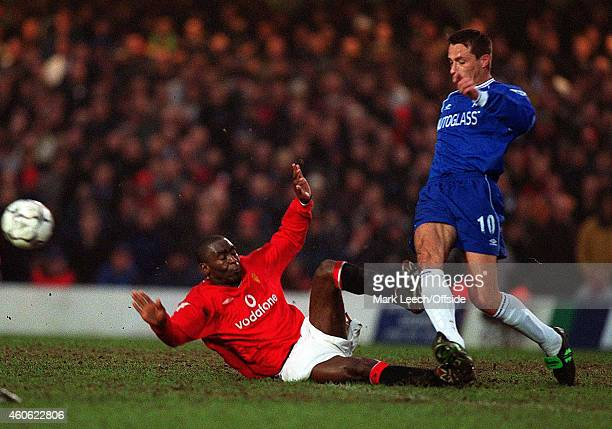 Andy Cole slides in and fouls Slavisa Jokanovic with a late tackle that earned the United player a yellow card during the Premiership match between...