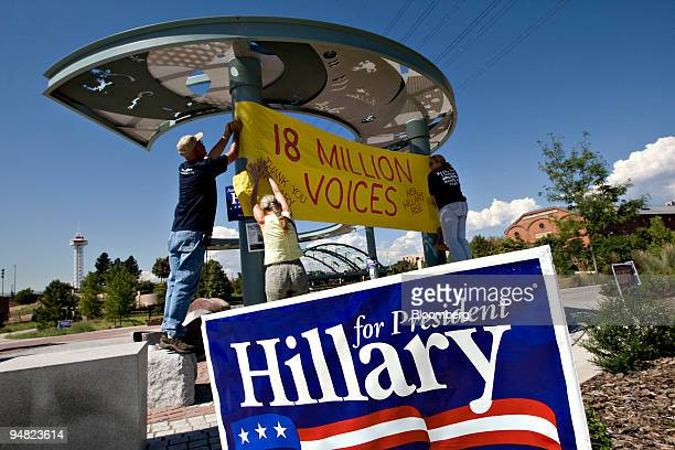 Andy Colon left Sharon Cassidy center and Sheila Johnson of 18 Million Voices Rise Hillary Rise hang a banner in Confluence Park in Denver Colorado...