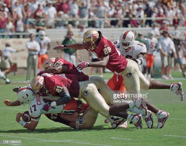 Andy Crosland, Kicker and Punter for the University of Miami Hurricanes is tackled by Linebacker Deon Humphrey, Defensive Back Shawn McCorkel, #55...