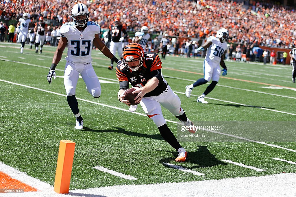 Andy Dalton #14 of the Cincinnati Bengals beats Michael Griffin #33 of the Tennessee Titans to the end zone to score a touchdown during the first quarter at Paul Brown Stadium on September 21, 2014 in Cincinnati, Ohio.