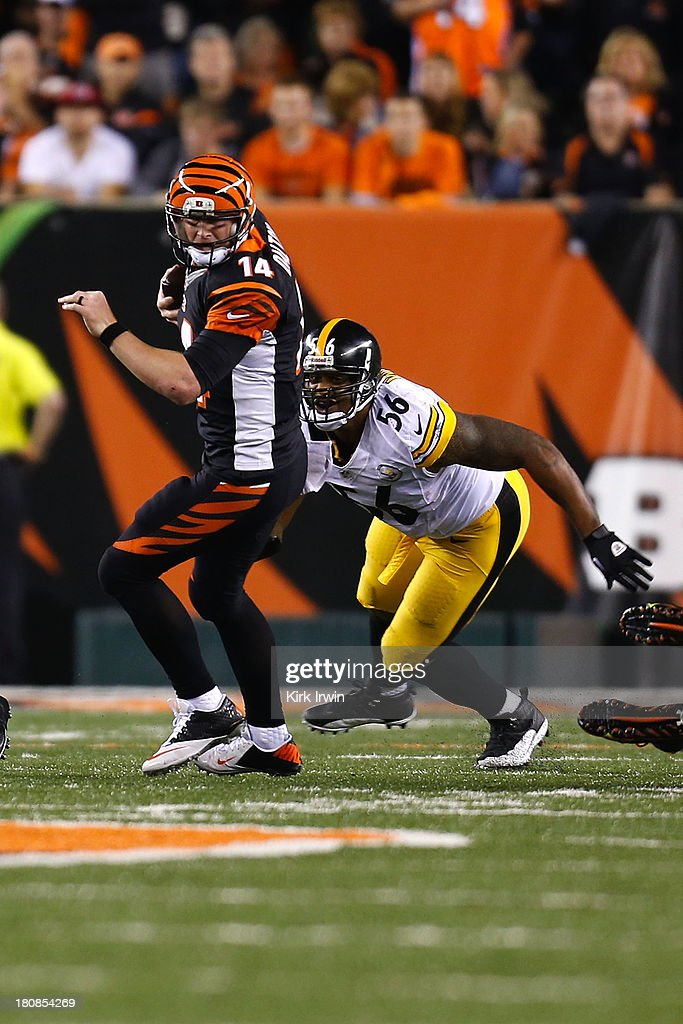 Andy Dalton #14 of the Cincinnati Bengals breaks a tackle by LaMarr Woodley #56 of the Pittsburgh Steelers during the fourth quarter on September 16, 2013 at Paul Brown Stadium on September 16, 2013 in Cincinnati, Ohio. Cincinnati defeated Pittsburgh 20-10.