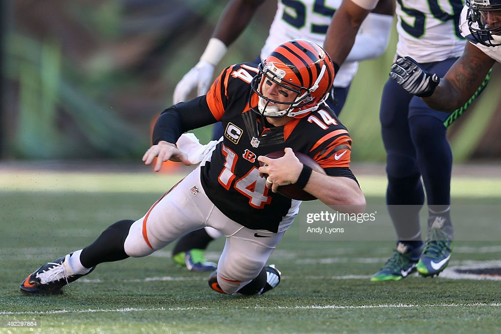 Andy Dalton #14 of the Cincinnati Bengals dives for positive yardage during overtime against the Seattle Seahawks at Paul Brown Stadium on October 11, 2015 in Cincinnati, Ohio. Cincinnati defeated Seattle 27-24 in overtime.