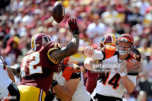 Andy Dalton of the Cincinnati Bengals is hit as he throws an interception caught by Rob Jackson of the Washington Redskins for a touchdown in the...