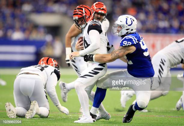 Andy Dalton of the Cincinnati Bengals is sacked by Margus Hunt of the Indianapolis Colts in the game against the Indianapolis Colts at Lucas Oil...