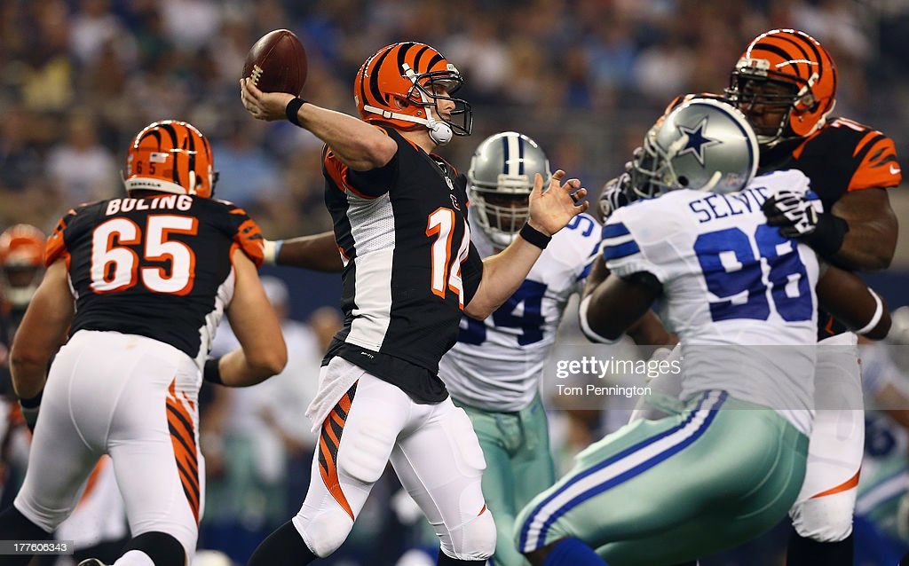 Andy Dalton #14 of the Cincinnati Bengals looks for an open receiver against the Dallas Cowboys in the second quarter during a preseason game at AT&T Stadium on August 24, 2013 in Arlington, Texas.
