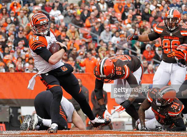 Andy Dalton of the Cincinnati Bengals runs for a first quarter touchdown past Armonty Bryant and Donte Whitner of the Cleveland Browns at FirstEnergy...