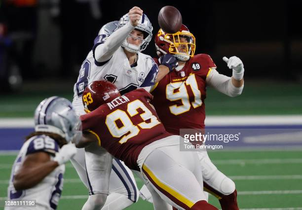 Andy Dalton of the Dallas Cowboys attempts to get a pass off against Jonathan Allen and Ryan Kerrigan of the Washington Football Team during the...