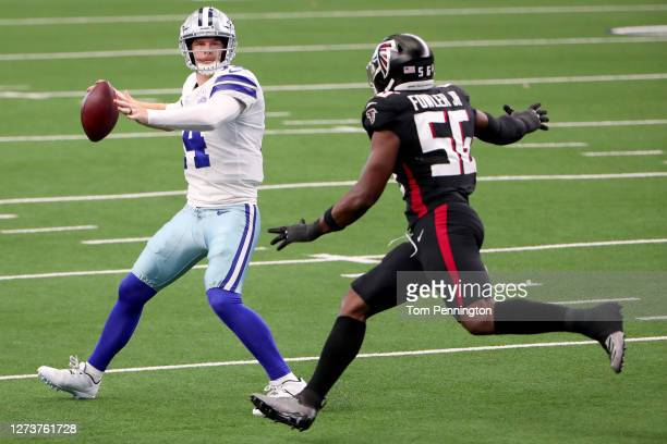 Andy Dalton of the Dallas Cowboys looks for an open receiver against Dante Fowler Jr. #56 of the Atlanta Falcons in the third quarter at AT&T Stadium...