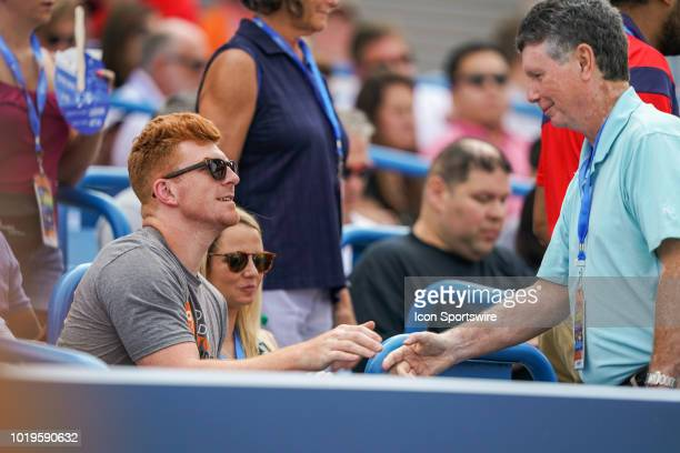 Andy Dalton quarterback of the Cincinnati Bengals shakes hands with Bill Cunningham radio talk show host for 700 WLW during the match between Simona...