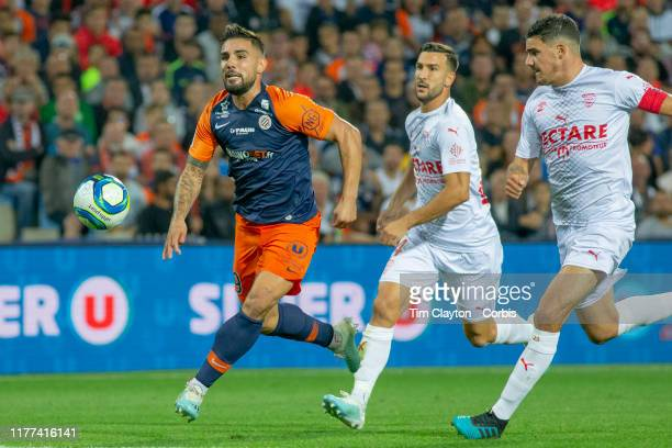 Andy Delort of Montpellier Pablo Martinez of Nimes and Anthony Briancon of Nimes challenge for the ball during the Montpellier V Nimes French Ligue 1...