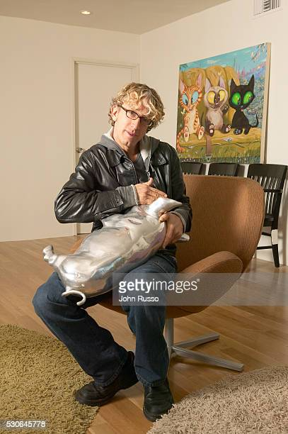 Andy Dick pantomimes nursing an oversized sterling piggy bank