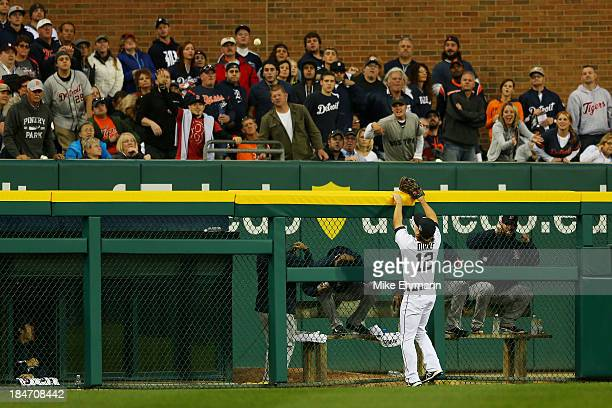 Andy Dirks of the Detroit Tigers looks on as a homerun hit by Mike Napoli of the Boston Red Sox goes over the wall in the seventh inning during Game...