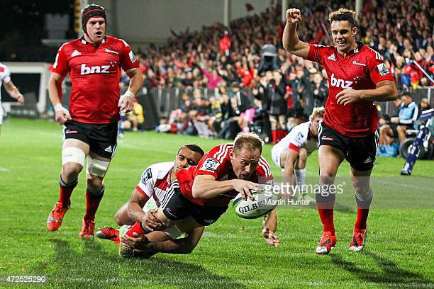 Andy Ellis of the Crusaders dives over to score a try in the tackle of Will Genia of the Reds during the round 13 Super Rugby match between the...