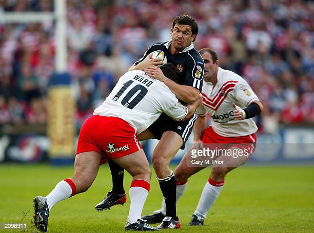 Andy Farrell of Wigan Warriors is tackled by Barry Ward of St Helens during the Tetleys Super League match between St Helens and Wigan Warriors held...